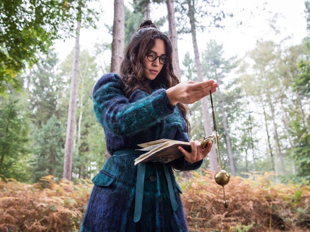 Anathema haciendo un ritual con un libro y un extraño artilugio