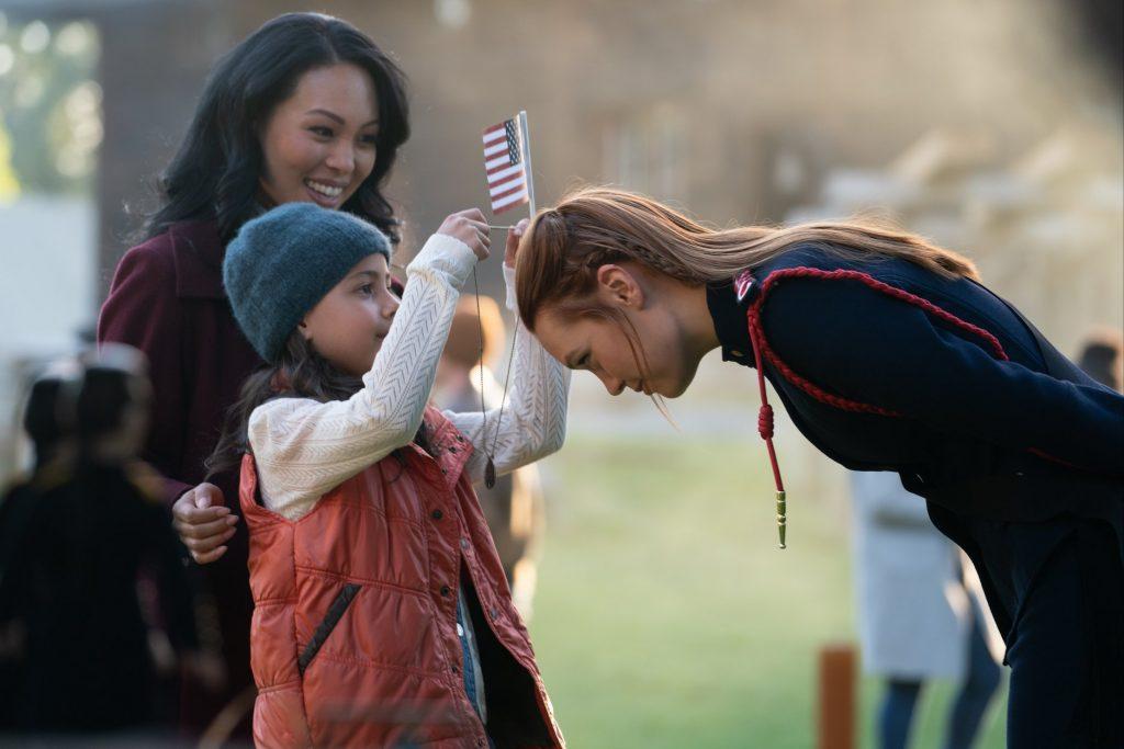 Una niña le pone una medalla a una de las protagonistas. Como medalla al honor o tal